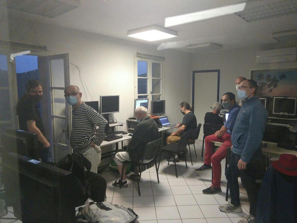 Photo du groupe prenant la pose, dans la salle informatique. Quelques écrans parmi les nombreux présents sont allumés, 3 personnes sont assis devant un écran.